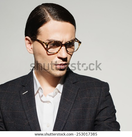 Portrait of a handsome man with glasses and a suit in the studio on a white background, concept of beauty and fashion, closeup - stock photo