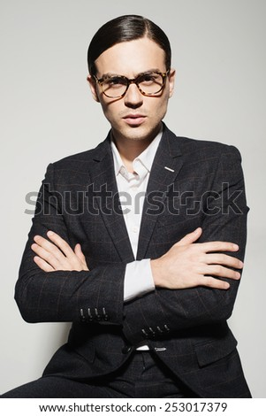 Portrait of a handsome man with glasses and a suit in the studio on a white background, the concept of fashion - stock photo