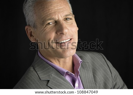 Portrait of a handsome man with grey hair smiling directly to the camera - stock photo