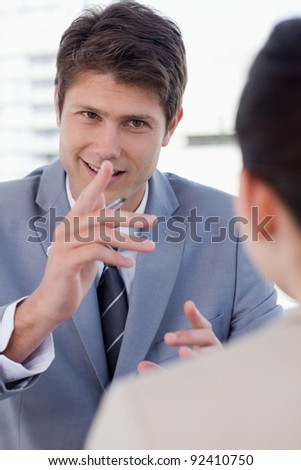 Portrait of a handsome manager interviewing a female applicant in his office - stock photo