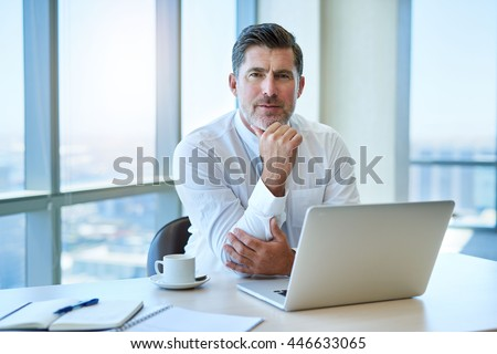 Portrait of a handsome mature business leader, sitting at his desk with his laptop, looking at the camera with a serious and engaging expression - stock photo