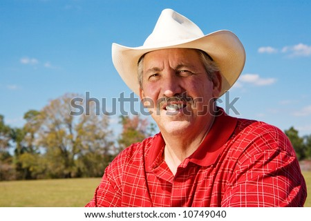 Portrait of a handsome, mature cowboy on his ranch.  Room for text. - stock photo