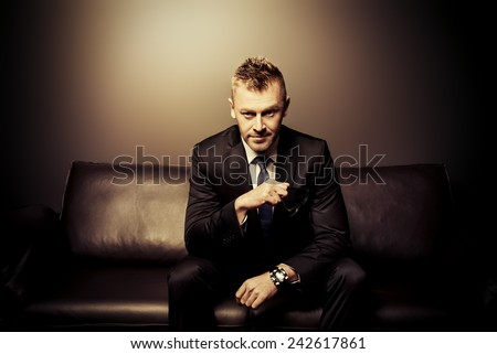 Portrait of a handsome mature man in elegant suit sitting on a leather couch in a luxurious interior.