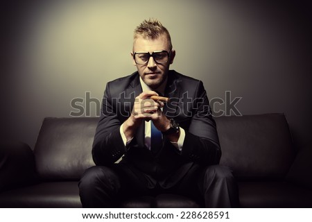 Portrait of a handsome mature man in elegant suit smoking a cigar. He is sitting on a leather couch in a luxurious interior.  - stock photo