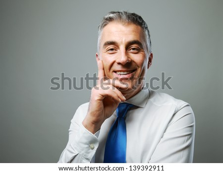 Portrait of a handsome mature man smiling on grey background - stock photo