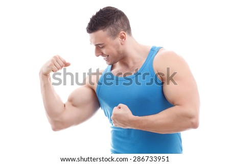 Portrait of a handsome muscled sportsman wearing blue shirt standing smiling and looking at his big biceps satisfied, isolated on a white background