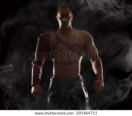 Portrait of a handsome muscular ancient warrior.Muscle man on dramatic light - stock photo