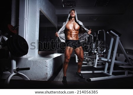 Portrait of a handsome muscular bodybuilder with muscular torso in hoodie posing in gym - stock photo