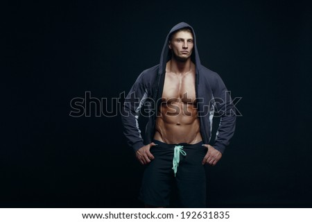 Portrait of a handsome muscular bodybuilder with muscular torso in hoodie posing over black background.  - stock photo
