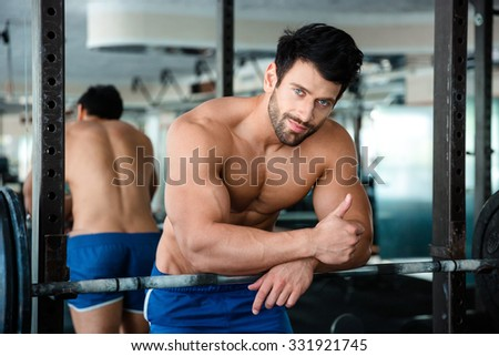 Portrait of a handsome muscular man showing thumb up in fitness gym - stock photo