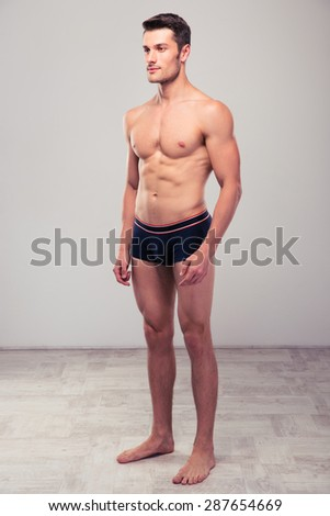 Portrait of a handsome muscular man standing in studio - stock photo