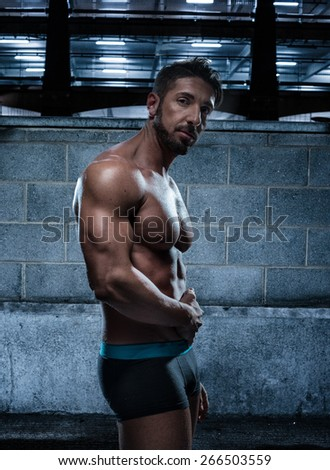 Portrait of a Handsome Muscular Man Wearing Boxer Brief Standing Inside an Old Building While Looking at Camera. - stock photo