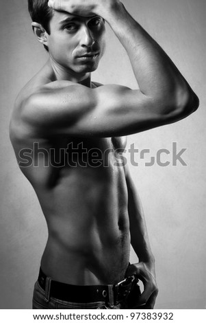 Portrait of a handsome muscular young man. Shot in a studio.black and white