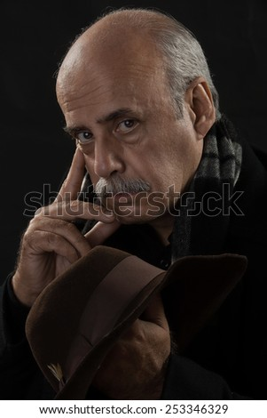 portrait of a handsome old man holding a cowboy hat - stock photo