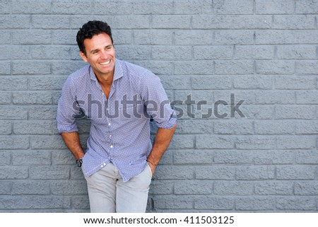 Portrait of a handsome older man laughing against gray background - stock photo