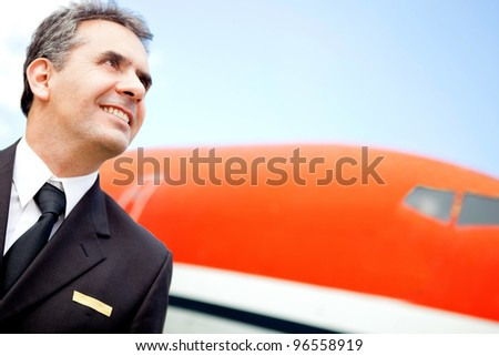 Portrait of a handsome pilot looking at the sky with an airplane at the background - stock photo