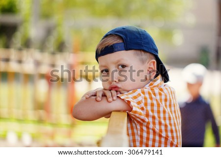 Portrait of a handsome sad little boy in cap looking at camera in park in sunny and summer day. - stock photo