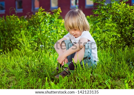 Portrait of a handsome sad little boy sitting on grass near his school - stock photo
