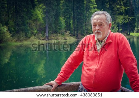 Portrait of a handsome senior man in bright sweater near the beautiful forest lake. Looking far away. Serious senior man with gray hair and beard on excursion. Horizontal image. - stock photo