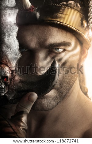 Portrait of a handsome serious man as ancient warrior holding sword - stock photo