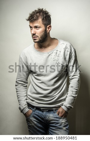 Portrait of a handsome serious young man standing against white background , fashion young man only ,  - stock photo