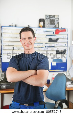 Portrait of a handsome smiling mechanic with arms crossed - stock photo