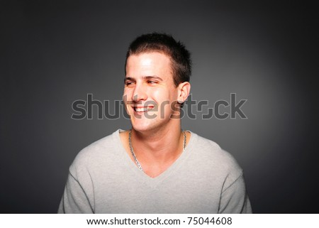 portrait of a handsome smiling young man over gray background - stock photo