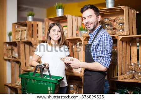 Portrait of a handsome store clerk giving some assistance to a customer at the supermarket - stock photo