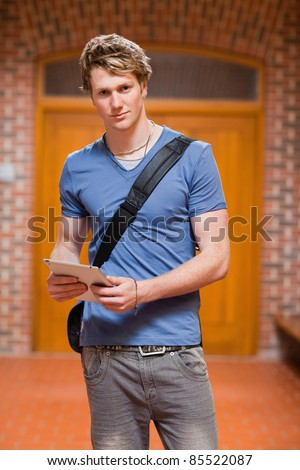 Portrait of a handsome student with a tablet computer in a corridor - stock photo