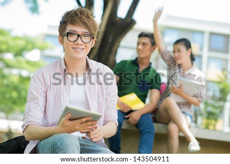 Portrait of a handsome students sitting with a tablet on the foreground - stock photo