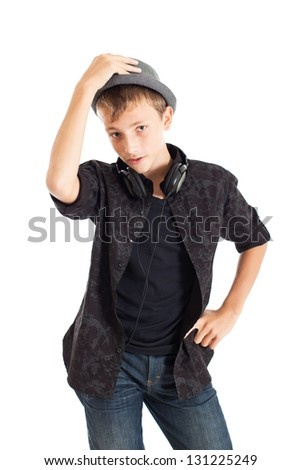 Portrait of a Handsome teen boy wearing a European black shirt, jeans and a hat. A boy holds his hand on his hat. Studio shot, isolated on white background. - stock photo