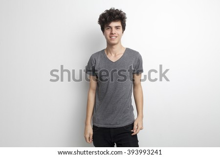 Portrait of a Handsome Teenager Standing, Smiling and Posing in the Studio - stock photo