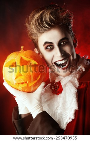 Portrait of a handsome vampire with pumpkin. Halloween. Dracula costume. - stock photo