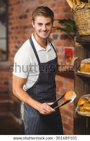 Portrait of a handsome waiter picking up a roll at the coffee shop