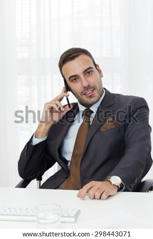 Portrait of a handsome well dressed young businessman sitting in a office and talking on the  smart phone.  - stock photo