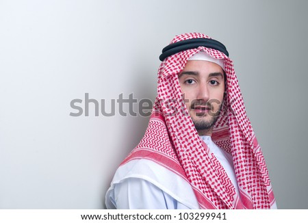 Portrait of a handsome young arabian business man leaning - stock photo