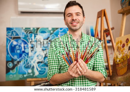 Portrait of a handsome young artist holding a bunch of paintbrushes in his workshop and smiling - stock photo