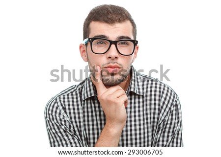 Portrait of a handsome young bearded man wearing a checkered shirt and glasses holding his finger near his face looking questionably, isolated on white background - stock photo