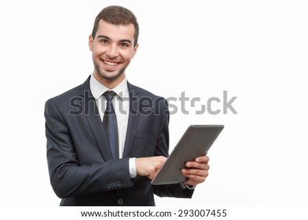 Portrait of a handsome young bearded man wearing a formal black suit holding a tablet looking at the camera and smiling, isolated on white background - stock photo