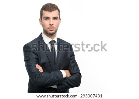 Portrait of a handsome young bearded man wearing a formal black suit standing crossing his arms looking serious, isolated on white background - stock photo