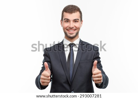 Portrait of a handsome young bearded man wearing a formal black suit standing smiling and showing his thumbs up, isolated on white background - stock photo