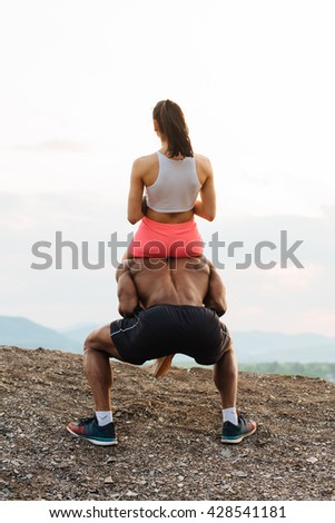 Portrait of a handsome young black african american man giving piggyback ride to his sexy girlfriend - stock photo