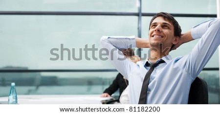 Portrait of a handsome young business man leaning against the window - stock photo