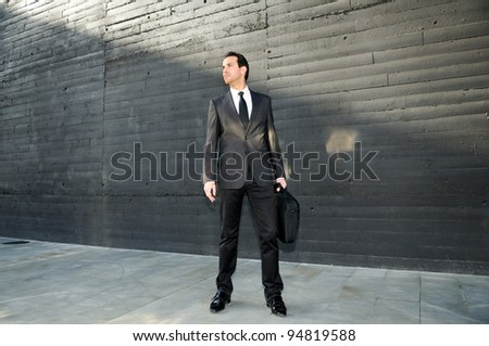 Portrait of a handsome young business man standing in the street with a briefcase - stock photo