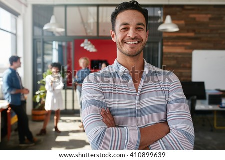 Portrait of a handsome young business man standing with arms crossed in an office. Smart caucasian young male designer with his colleagues in background. - stock photo