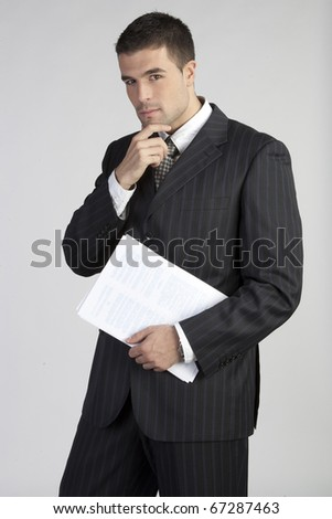 Portrait of a handsome young business man thinking - stock photo