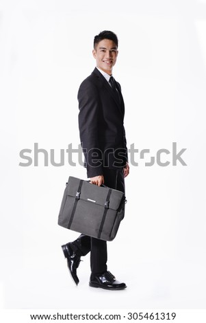 Portrait of a handsome young business man walking carrying a suitcase  full body - stock photo