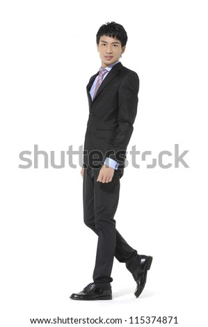 Portrait of a handsome young business man walking �full body - stock photo
