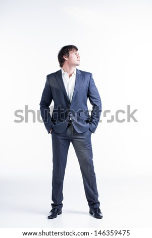 portrait of a handsome young business man wearing a gray suit looking skywards with his hands in his pockets - stock photo