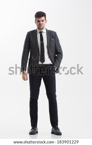 Portrait of a handsome young businessman in nice dark gray suit. Hands in his trouser pockets.